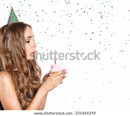 Festive woman with cake blow out the candles on a background of confetti - stock photo