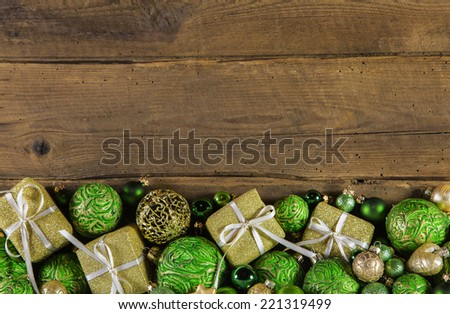Festive wooden christmas background with golden presents and green balls. - stock photo
