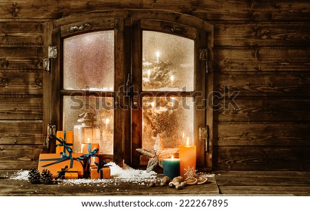 Festive wooden Christmas cabin window with gift-wrapped colorful orange presents, burning candles and decorations in winter snow and a glimpse of a decorated Christmas tree through the frosted window - stock photo