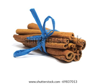 Festive wrapped cinnamon sticks on the white background - stock photo