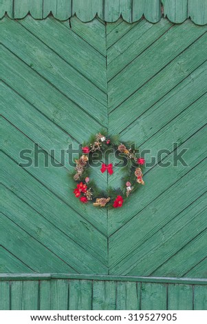 Festive X-mas outside wreath is hanging on old rustic green door - stock photo