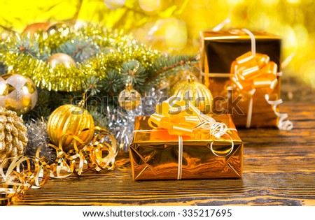 Festive yellow and gold Christmas background with elegant foil wrapped gold gifts and golden baubles on a pine branch, rustic wood background - stock photo