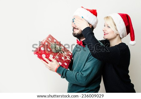 Festive young couple exchanging presents - stock photo