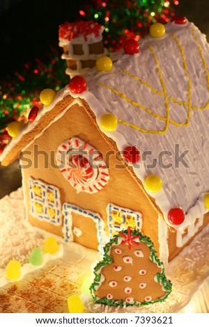 festively lit homemade gingerbread house with Christmas tree and decorations - stock photo