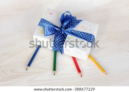 festively wrapped gift with children's drawings in pencil/Painted a gift with their own hands - stock photo