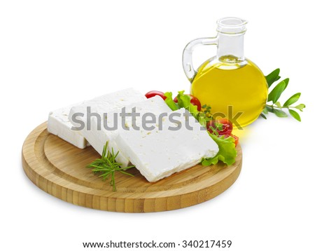 feta cheese(Greek product) slices on a wooden serving board decorated with fresh vegetables and a bottle of olive oil