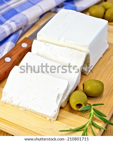 Feta cheese, knife, rosemary, olives, blue checkered napkin on the background of wooden boards - stock photo