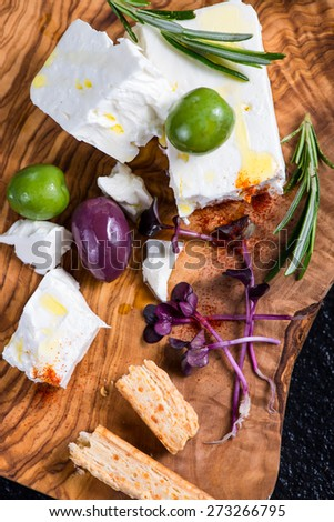 Feta cheese on wooden board with olives and oil and herbs