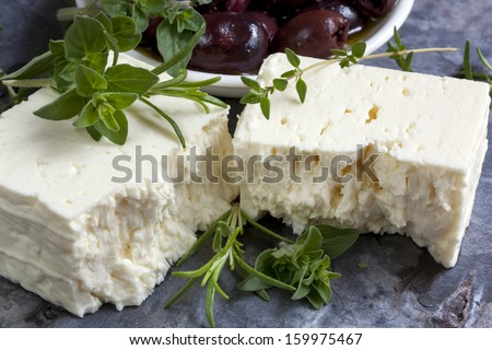 Feta cheese with black olives and fresh herbs.