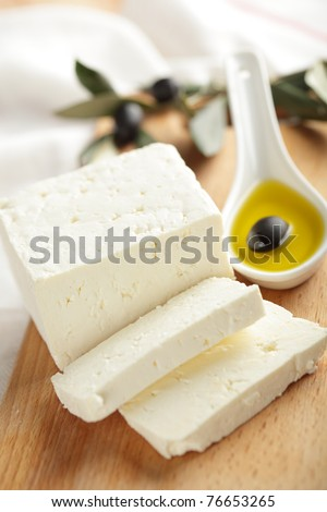 Feta cheese with black olives in olive oil - stock photo