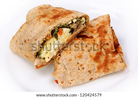 Feta Egg Wrap Close Up on White Plate Cut in Halves - stock photo