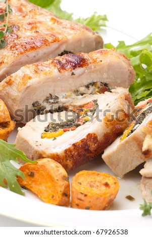 Feta-, spinach-, and bell pepper - stuffed pork tenderloin roulade garnished with sweet potato and green salad. - stock photo