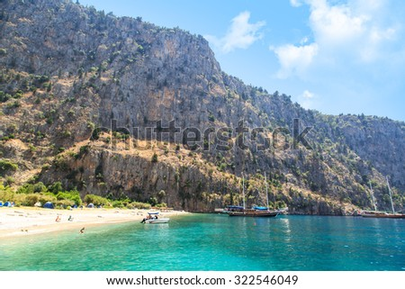 FETHIYE, MUGLA - JULY 17, 2015 : Butterfly Valley, natural cove of Fethiye famous with big butterflies, seascape with boats and people in the sea. - stock photo