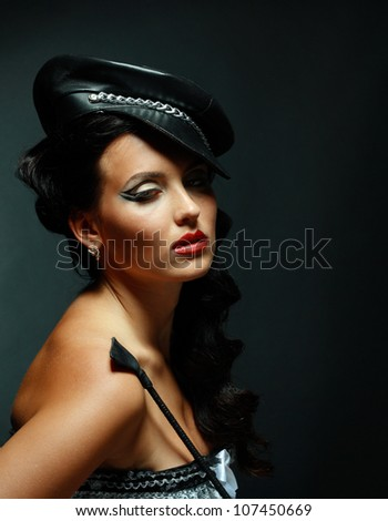 Fetish model in sexy outfit with Strict Leather Short Handle Wide Head Riding Crop - stock photo