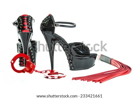 Fetish stuff: hand cuff, whip and extreme high heels shoes - stock photo