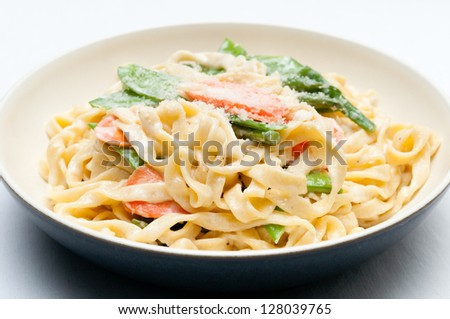 fettuccine alfredo primavera, creamy sauce with vegetables and home made pasta - stock photo