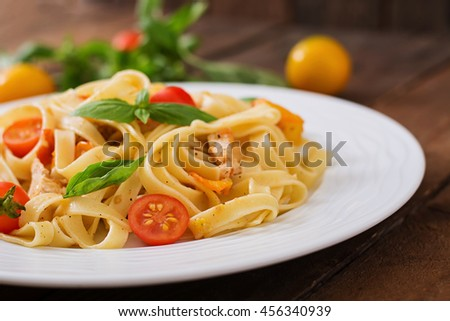 Fettuccine pasta in tomato sauce with chicken, tomatoes decorated with basil on a wooden table - stock photo