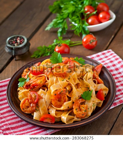 Fettuccine pasta with shrimp, tomatoes and herbs - stock photo