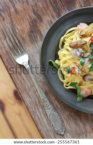 Fettuccine with seafood, chili and parsley on a tin plate. - stock photo