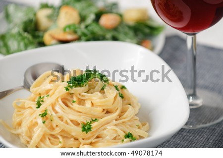 Fettuccini Alfredo with Ceasar Salad and wine - stock photo