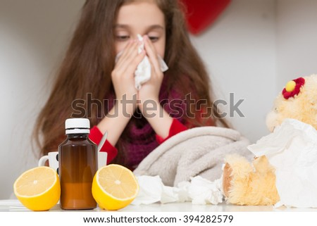 Fever, cold and flu concepts. Close-up of medicines represented on table while pretty sick girl blowing and cleaning her nose in tissue in on the background. - stock photo