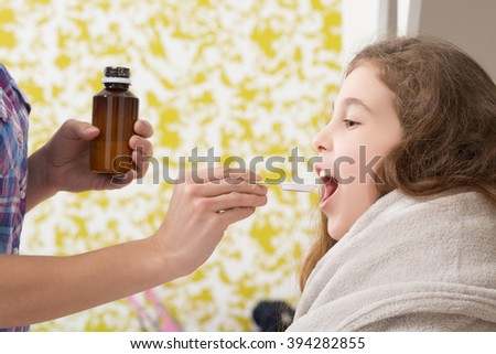 Fever, cold and flu concepts. Close-up picture of little lady receving medicines from her mother to feel better and fine. - stock photo