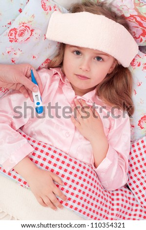 Fever, cold and flu - Mother is caring about sick child in the bed - stock photo