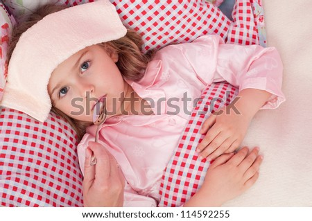 Fever, cold and flu - mother is giving medicines to the sick child - stock photo