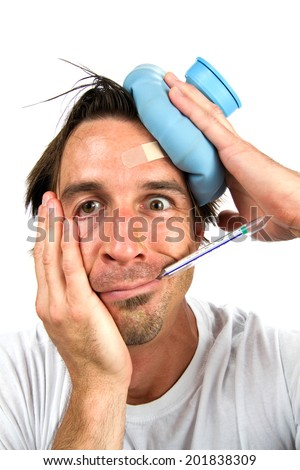 Feverish sick man holds water bottle to head while he takes his temperature with a thermometer in his mouth. - stock photo