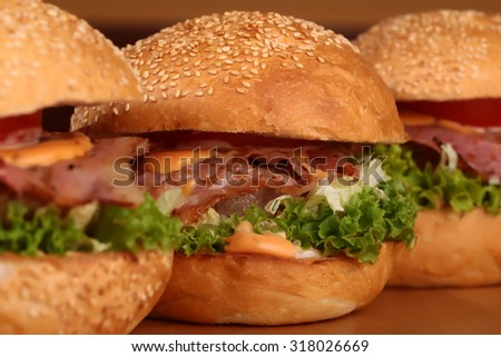 Few appetizing big delicious fresh burgers with green lettuce red tomato cheese cabbage bacon slice meat cutlet and white bread bun with sesame seeds on black background closeup, horizontal picture - stock photo