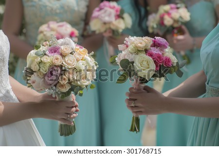 Few beautiful fresh wedding posies of colorful rose flowers pink violet lilac purple white orange and yellow in hands of bride and bridesmaid in blue dresses, horizontal picutre - stock photo