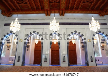 few big beautiful lustres in a hall of Grand Mosque in Oman. the lights is on. - stock photo