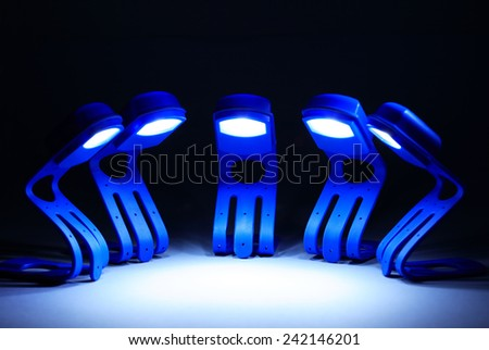 Few  blue glowing lamps in a row on dark background - stock photo
