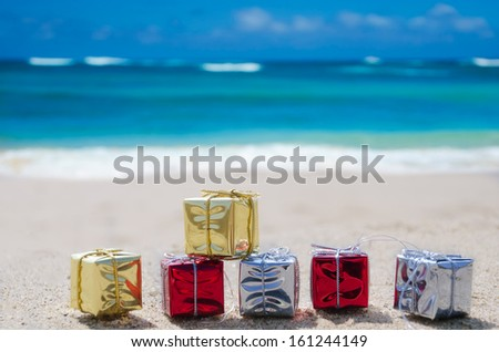 Few Christmas gift box on the sandy beach by the ocean - stock photo