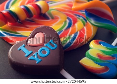 Few colorful lollipops and chocolate heart against gray background. - stock photo