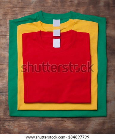 Few colorful t-shirts different size on the wooden background