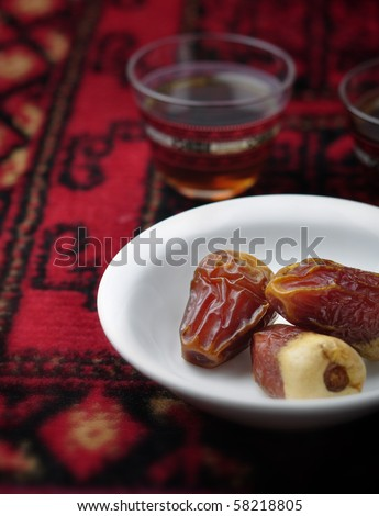 few dates in a bowl and tea cup on red carpet - stock photo