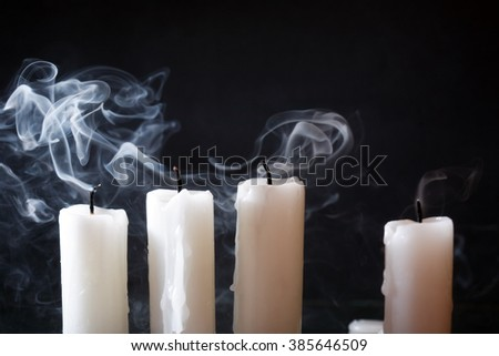 Few extinguished candles in a row on dark background - stock photo