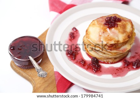 few fresh pancakes with a strawberry sauce on a dish