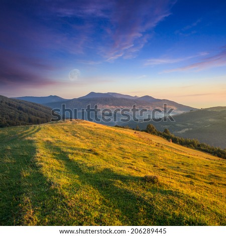 few haystacks behind wooden fence and some trees on a green meadow on hillside between mountain at sunset with moon - stock photo