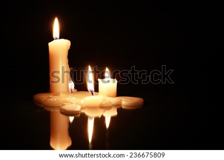 Few lighting candles on dark background with reflection - stock photo