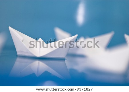 Few paper origami boats floating in blue water - stock photo