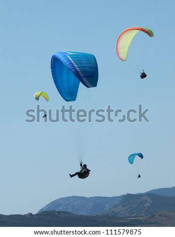 few paragliders in the blue sky above the rocks - stock photo