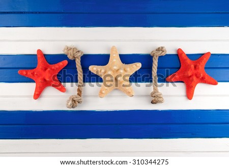 Few sea stars and rope cuts on a wooden background. - stock photo