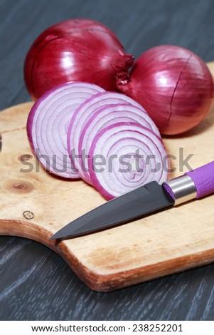Few slices of raw onion near knife on cutting board - stock photo