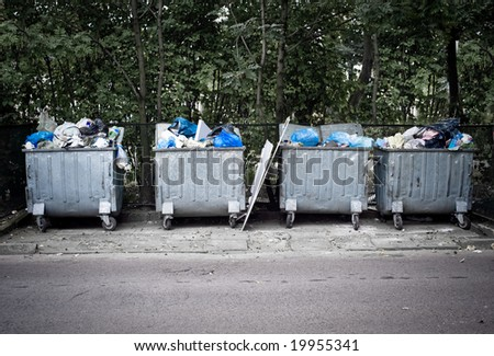 Few trashcans full of garbage, standing over trees - stock photo