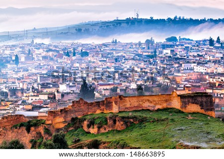 Fez, Morocco aerial view on a frosty foggy winter morning. The ancient city wall is in the foreground and behind it, an overview of the old neighborhood. - stock photo