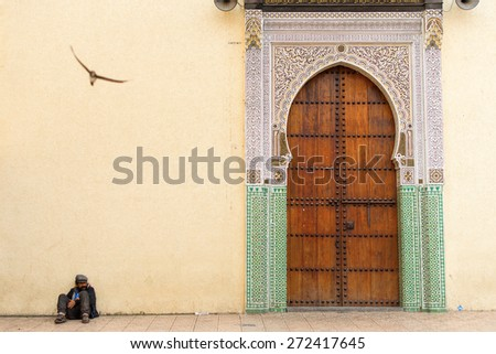 FEZ, MOROCCO - APRIL 15: Unkown man relaxing near to entrance of mosque, with traditional mosque door on April 15, 2015. - stock photo