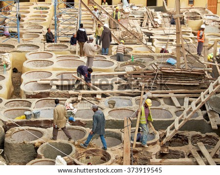 Fez, Morocco - December 14, 2015: Laborers working on rehab in the Chouwara tanneries in Fes Medina. Restoration program of historic monuments have the objective to give new life to historical places. - stock photo