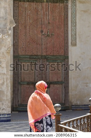 FEZ, MOROCCO - JULY 19: A woman in a souk on July 19, 2014 in Fez, Morocco. The medina is listed as a UNESCO World Heritage Site and is believed to be one of the world's largest car-free urban areas. - stock photo